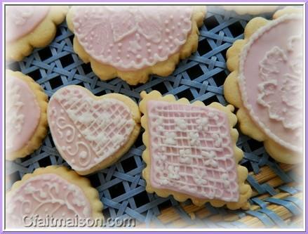Biscuits avec glaçage royal rose et dessins réalisés sur ce glaçage en  glaçage blanc.